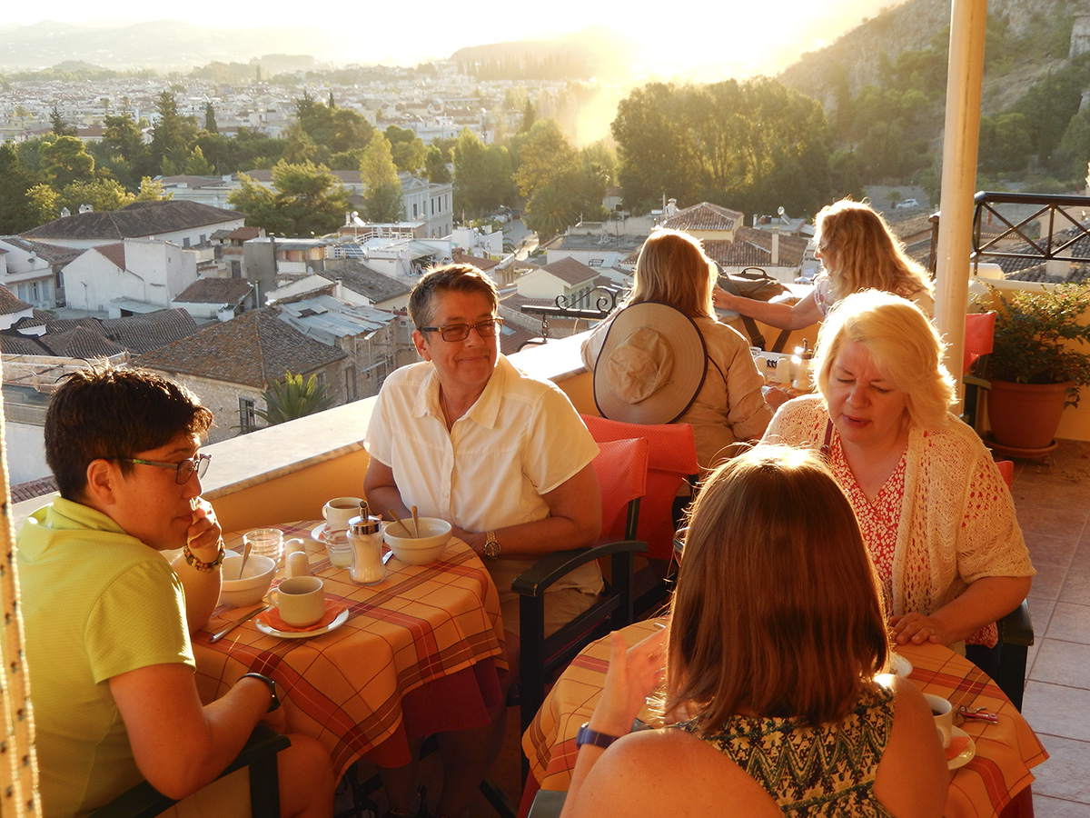 Southern Greece Tour (2014) participants enjoying a sunrise breakfast and spectacular views on the outdoor terrace of the charming Pension Marianna in Nafplio.